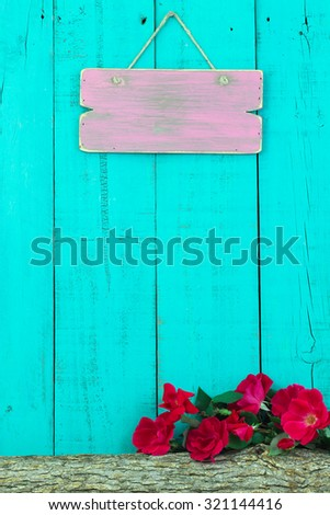 Blank pink sign hanging over log with red flowers with antique teal blue wood background - stock photo