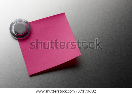 Blank pink stickie note tacked onto metal surface with magnet - stock photo