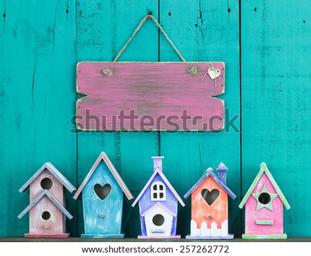 Blank pink wooden sign hanging over row of colorful birdhouses on antique teal blue wood background - stock photo