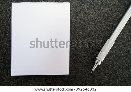 Blank post it paper book with pencil, on black sandpaper texture