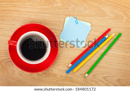 Blank post-it with office supplies and coffee cup on wooden table. Above view - stock photo