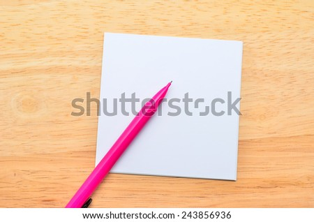 Blank post-it with pen on office wooden table. Above view - stock photo