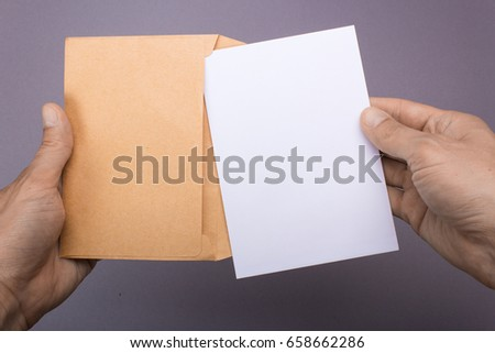Blank postcard and envelope in hands on a gray background. Leaflet A6 mockup