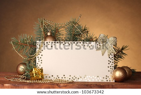 blank postcard, Christmas balls and fir-tree on wooden table on brown background - stock photo