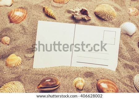 Blank postcard in hot beach sand with some sea shells, copy space for summer holiday vacation message.