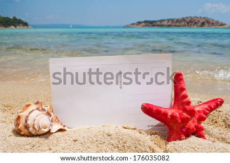 Blank postcard on the sandy beach and horizon over sea in the background, decorated with starfish and seashell - stock photo