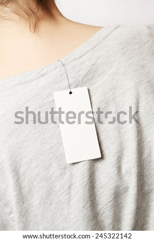 Blank price tag, Blank price tag on the woman t-shirt- view from the back - stock photo