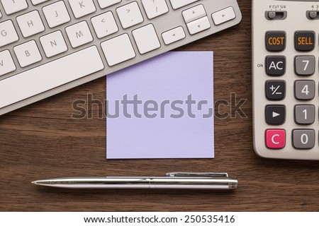 Blank purple notepad putting under keyboard. Pen and calculator on wood table - stock photo