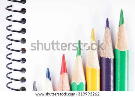blank realistic spiral notepad notebook with colorful pencils on white background - stock photo
