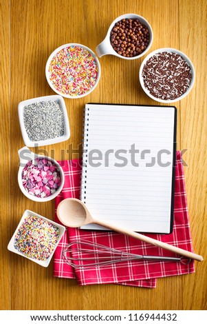 Blank recipe book with a variety of candy sprinkles. - stock photo