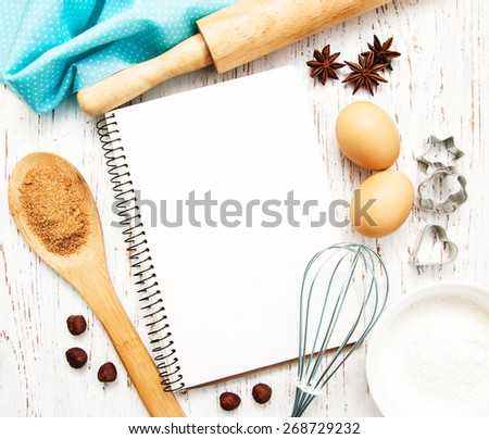 blank recipe book with baking ingredients on a old wooden background - stock photo