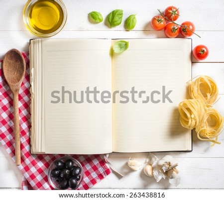 Blank recipe cooking book and ingredients on white table,selective focus and above  - stock photo