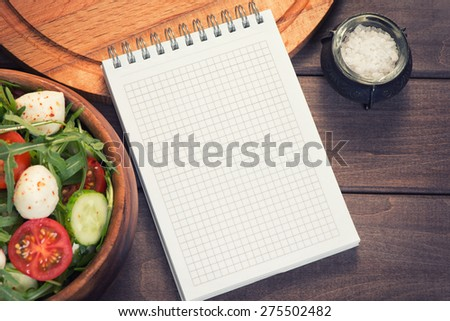 blank recipe notepad and arugula salad with mozzarella - stock photo
