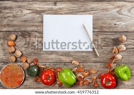 Blank recipe paper on wooden background with vegetables - stock photo