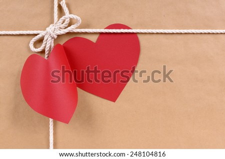 Blank red heart shape valentine card or gift tag on a brown paper package background tied with string.  Space for copy. - stock photo