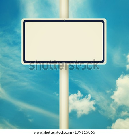 Blank road signs, empty street post, blue sky background in vintage style. - stock photo