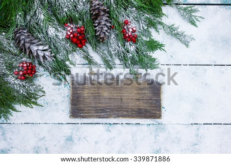 Blank rustic sign with Christmas tree garland border on antique teal blue snowy wood background