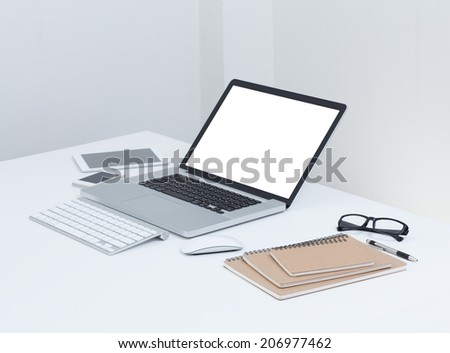 blank screen laptop computer with notebook on the table
