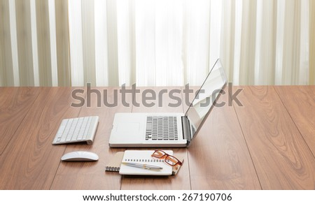 Blank screen laptop computer with office accessories on wooden table; window light effected