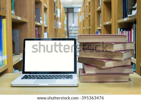 Blank screen laptop computer with old book in library room - stock photo