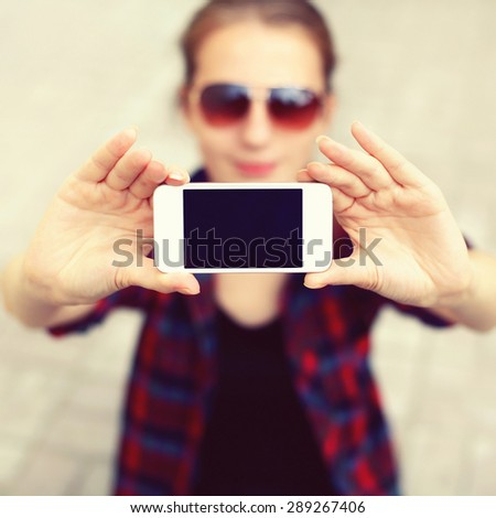 Blank screen phone, woman makes self-portrait on the smartphone, female face blurred, close-up hands showing display - stock photo