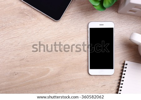 Blank screen smartphone, tablet and office supplies on wooden background