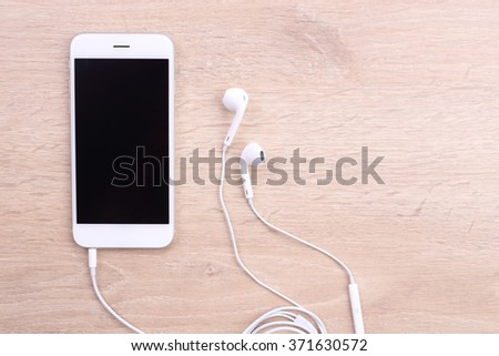Blank screen smartphone with earphone on wooden background - stock photo