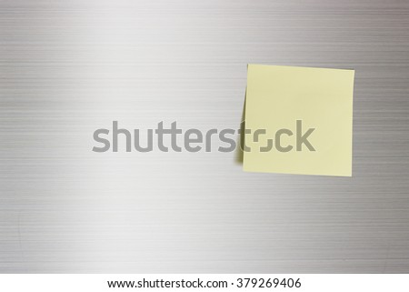 Blank sheet of a light yellow paper on a fridge door. For leaving someone in your house a message, reminder, idea, words, info, phrase, letter, news, etc when you are not at home or coming back late. - stock photo
