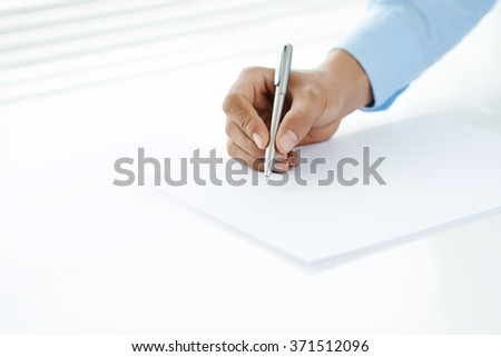 Blank sheet of paper and hand with pen