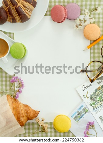 Blank sheet of paper for notes on a checkered tablecloth with coffee, macaroon, croissants and postcards in the French style
