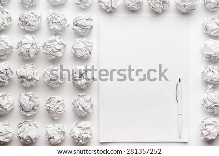 blank sheet of paper on the white table with a pen creative process concept - stock photo