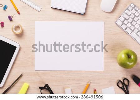 Blank sheet of paper on wooden office desk. - stock photo