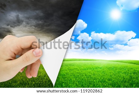 Blank sheet of paper with hand opening it. Storm changes to good weather. Nature background - stock photo