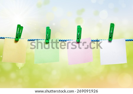 Blank sheets of paper hanging on a rope on green background