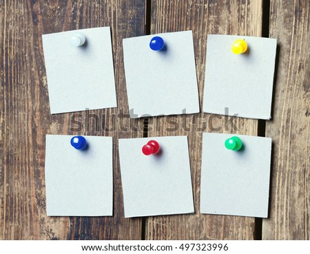 blank sheets of paper pinned colored buttons to wooden wall.toned