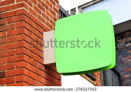 Blank sign against red brick wall - stock photo