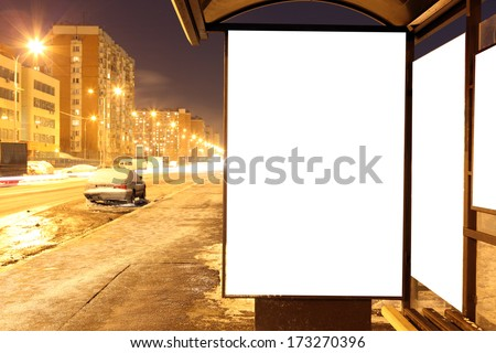 Blank sign at bus stop at evening in city - stock photo