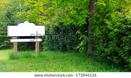 Blank sign with wooden posts surrounded by trees in the summer. - stock photo