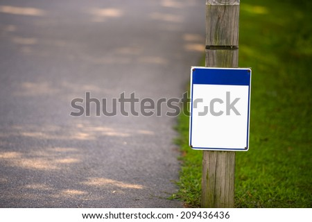 Blank signboard on green grass in park to place your logo or advertising on it - stock photo