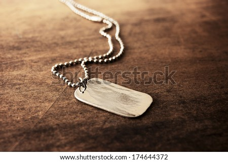 Blank silver tag on a ball chain, on a old wooden desk.   - stock photo