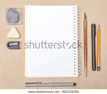 blank sketchbook page mock up with pen and eraser on craft paper background - stock photo