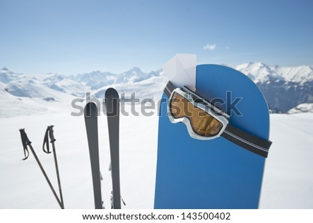 Blank ski pass and winter sport equipment such as ski and snowboard waiting on top of mountain ready for you. Concept to illustrate ski admission fee - stock photo