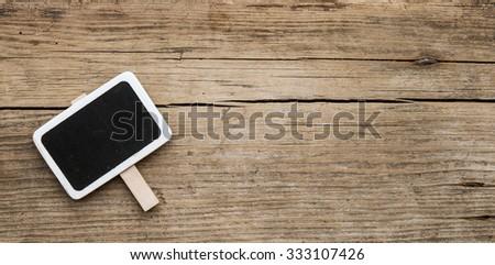 blank small black chalkboard on wood background - stock photo
