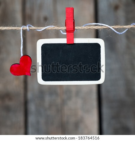 Blank small blackboard and small red heart hanging on the clothesline. On old wood background. - stock photo