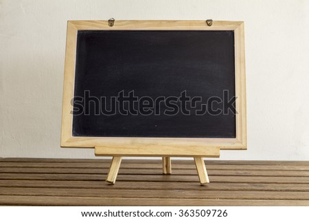 blank small blackboard on the wooden table - stock photo
