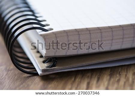 Blank spiral notebook on an oak wood table - stock photo