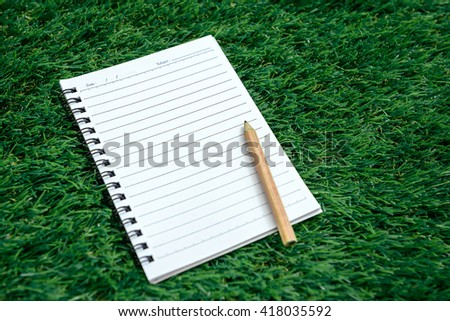 Blank spiral notebook with line paper and pencil on green grass - stock photo