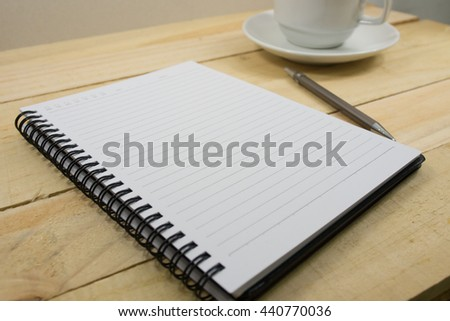 Blank spiral notebook with line paper on wood table - stock photo