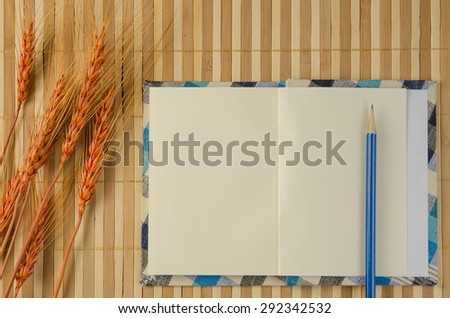 blank spiral notepad notebook on brown bamboo background - stock photo