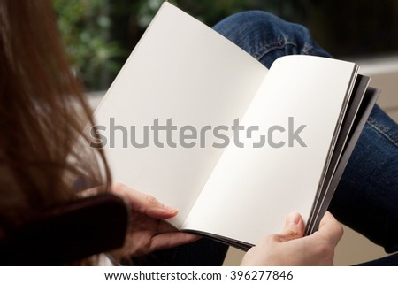 Blank spread, open book in woman's hands